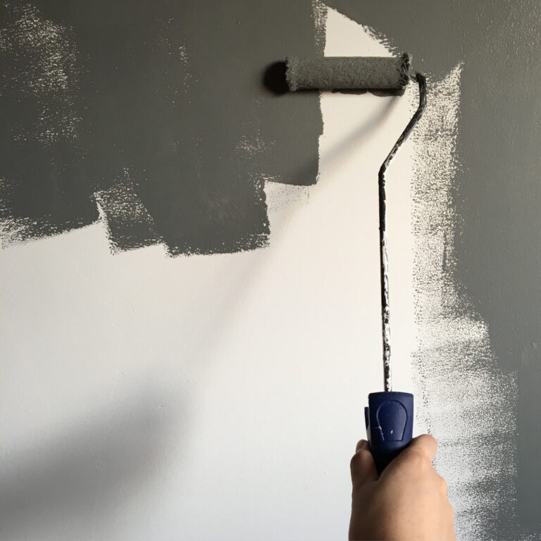 person-holding-paint-roller-while-painting-the-wall-994164